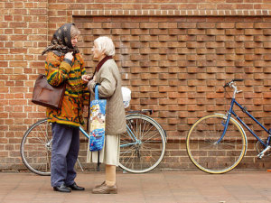 Old women talking outside by bicycles