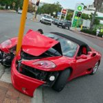 Wrecked Red Ferrari at street post