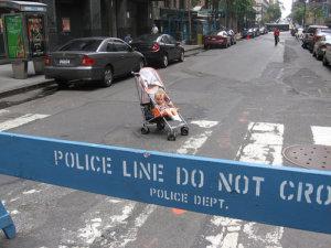Baby in Stroller behind Police Line