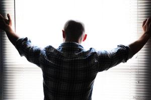 Bald man in plaid shirt at window