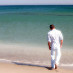 Man in all white outfit on beach shore